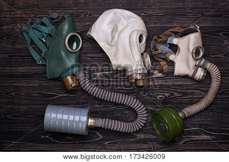 Three different retro gas mask on wooden background.Top view