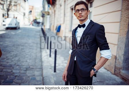 Portrait of fashionable well dressed man posing outdoors looking away.