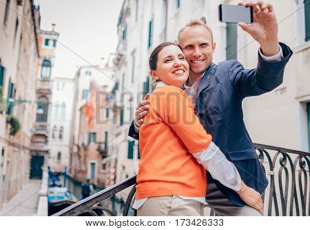 Loving couple take a selfie on the one of bridge over a channel in Venice