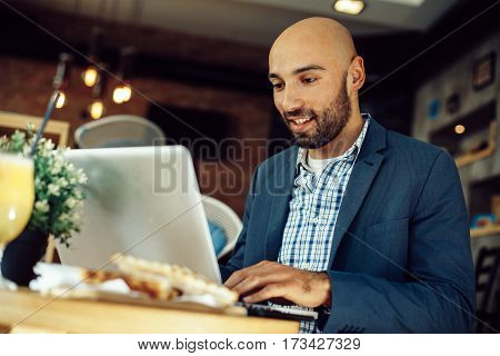 Modern man uses a laptop in a cafe