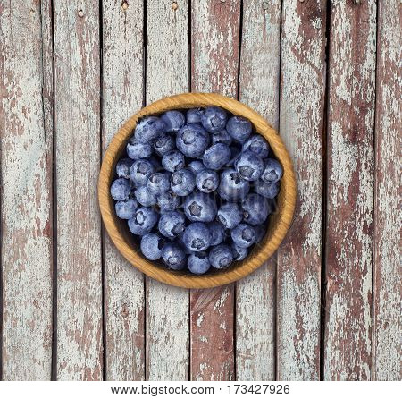 Blueberries in a wooden bowl. Top view. Ripe and tasty blueberries on a wooden background. Blueberries on wooden table with copy space