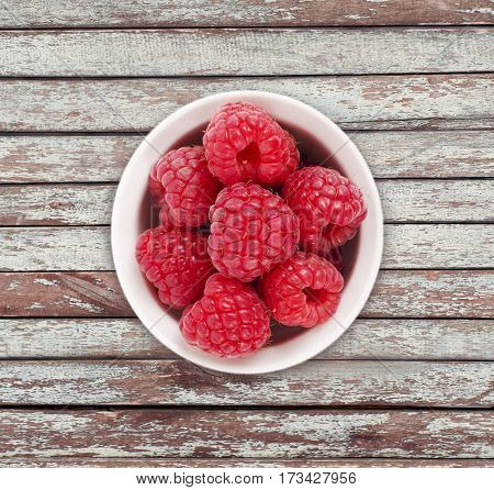 Raspberries in a white ceramic bowl. Top view. Ripe and tasty raspberries on a wooden background. Raspberries on wooden table with copy space