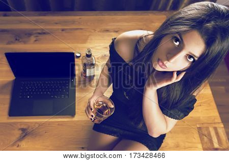 Brunette woman sitting on wooden office - Young woman wearing a sexy black dress holding a glass of whiskey in hand and sitting near the laptop on a wooden office