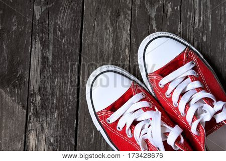 old red sneakers on old wooden background