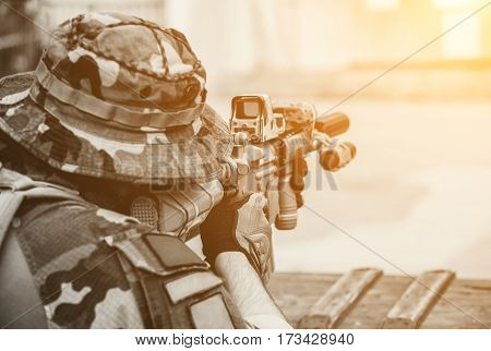 soldier in the performance of tasks in camouflage protective gloves helmet holding a machine gun takes aim for shot. War Zone.