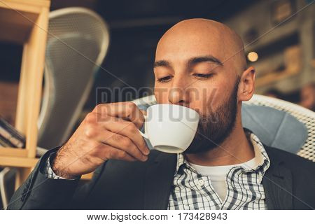 Close up portrait of man drinking coffee in cafe