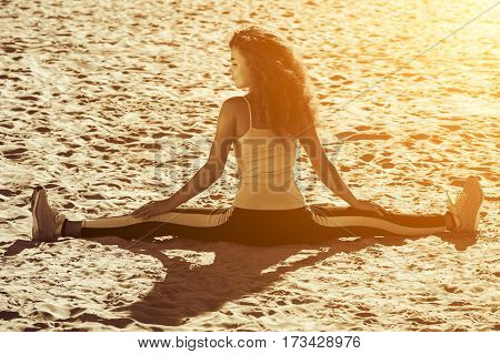 Young athletes - gymnast with curly hair and sneakers doing the splits on the beach in summer morning exercise. Sports concept reducing weight loss and a healthy lifestyle.