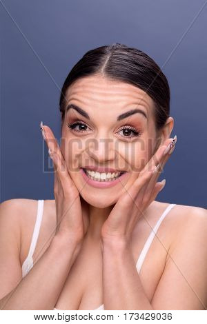 people skincare and beauty skin concept - face of beautiful happy young woman with wrinkles on her forehead