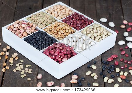 Sources of protein: lentils, beans, kidney beans, chickpeas on wooden table