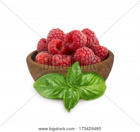 Raspberries in a wooden bowl isolated on white background. Raspberry with basil close-up. Vegetarian or healthy eating. Juicy and delicious raspberries