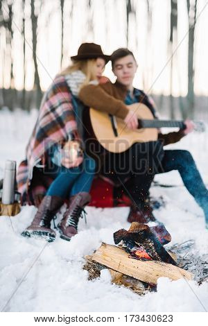 hipster stylishly dressed young couple in a warm blanket sit by the fire in the winter forest