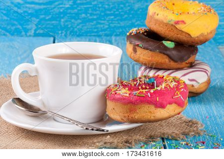 pile of glazed donuts with a cup of tea on a blue wooden background.