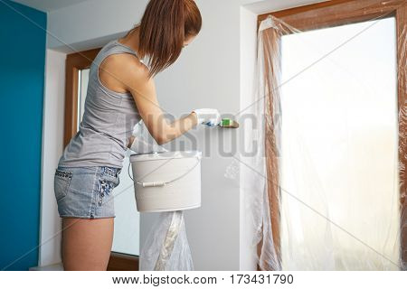 Portrait of female painter near wall before painting.