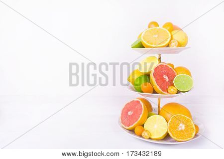 Different citrus fruit (orange lemon lime grapefruit kumquat) on cake stand with copy space on the white background