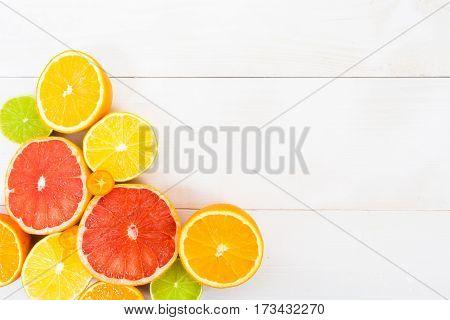 Cut different citrus fruit (orange lemon lime grapefruit kumquat) on the white wooden board with copy space