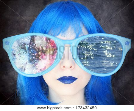 Girl with blue hair in huge eyeglasses. Portrait of a girl in a blue wig
