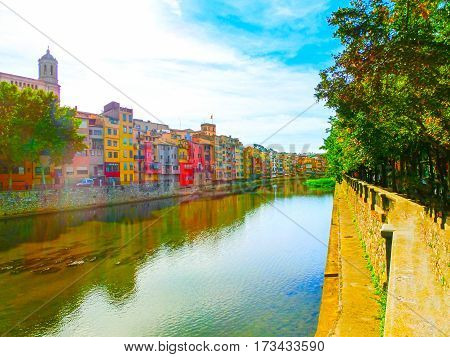 Colorful yellow and orange houses reflected in water river Onyar, in Girona, Catalonia, Spain.