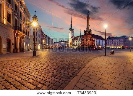 Town hall and Holy Trinity Column in Olomouc Czech Republic during sunset.