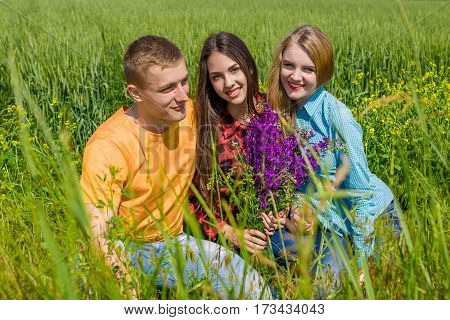 Beautiful Two Girls And Guy On Field With Wildflowers