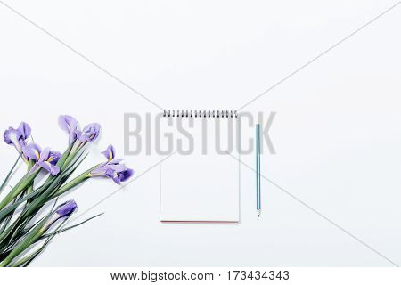 Bouquet Of Irises And Notebook With Pencil On A White Table