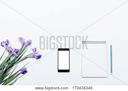Bouquet Of Violet Irises, Mobile Phone And Notebook With Pencil On A White Table