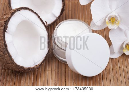 jar of coconut cream near the halves of coconut and orchids