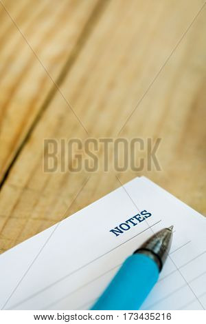 White Note With Notes Word Over Rustic Wooden Background