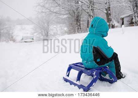Little boy sitting on a sleigh. Around a lot of snowWinter landscape on mountain.Winter landscape on mountain