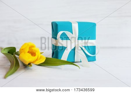 Yellow tulip and a box with a gift. Concept of holiday birthday Easter March 8.