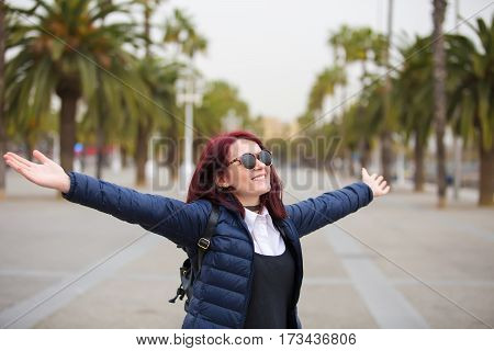 Happy excited woman with raised hands in Barcelona city.Young girl with raised hands feeling happy and free.Life style