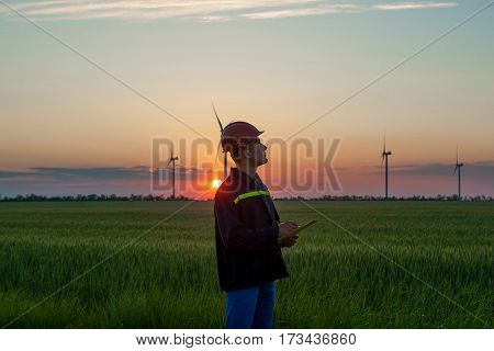 Engineer in wheat field at sunset checking on turbine production