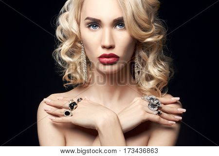 Fashion beauty Nude blonde woman on a dark background. Girl with jewels on the arms and neck. Skin care and beautiful makeup perfect girls. Luxury woman with elegant curly hair
