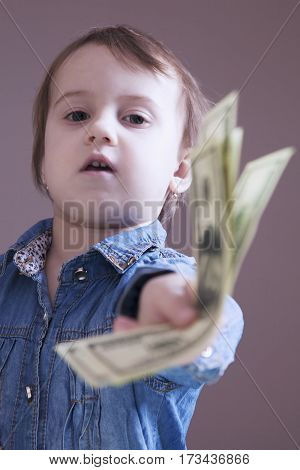 Make Millions By Loaning Money. Business baby girl giving you loan dollars for profit. Humorous photo. (wealth freedom success profit dependency power)