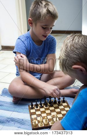 Photo of two young kids playing chess.
