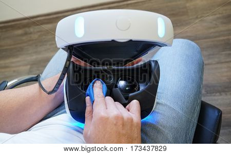 Man cleaning virtual reality glasses sitting on the chair in the room wearing white t-shirt and blue jeans top view. Male hands holding virtual reality goggles VR selective focus top view