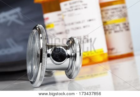 Macro photo of a stethoscope with pill bottles and x ray in the background.