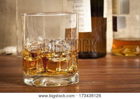 Close up photo of a glass of alcohol on a wood table with bottles in the background.