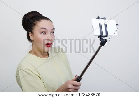 a girl with a stick for селфи takes pictures itself