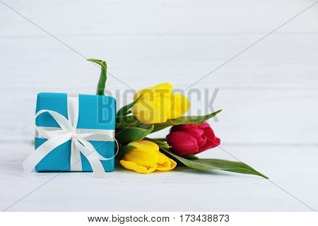 Packaged gift and spring flowers. Concept of holiday birthday Easter March 8.