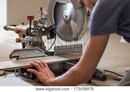 a man with a Board and miter saw closeup concept building and repair