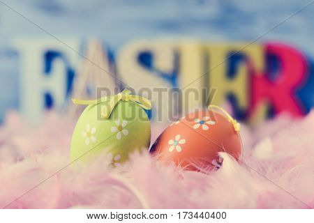 closeup of some decorated eggs surrounded by soft pink feathers and three-dimensional letters forming the word easter in the background, against a blue background