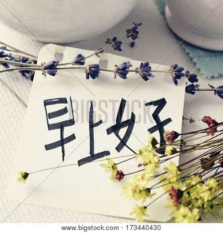 closeup of a note with the text good morning written in chinese on a table set for breakfast with some porcelain pottery and some flowers