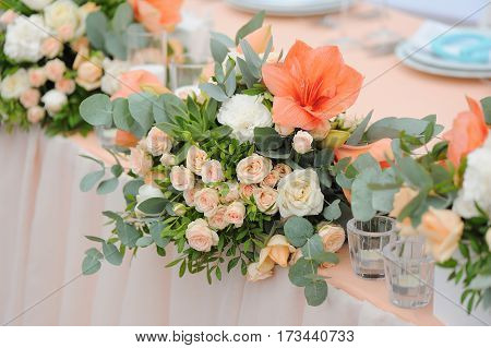 Newlyweds table decorated with bouquet and candles, in peachy colours with monogram