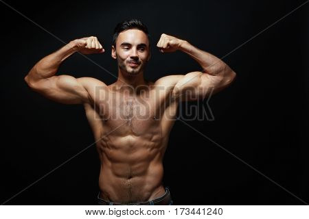 half length portrait of happy young man showing his big muscles standing next to color background in photostudio