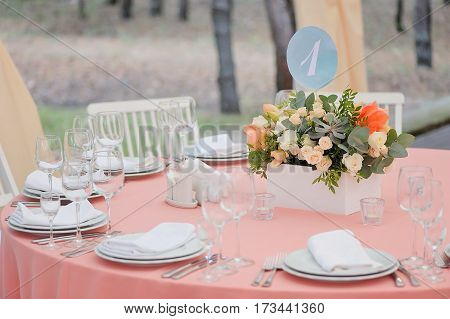 Wedding guest numbered table, decorated with bouquet and settings, in biege and light blue and pink colours