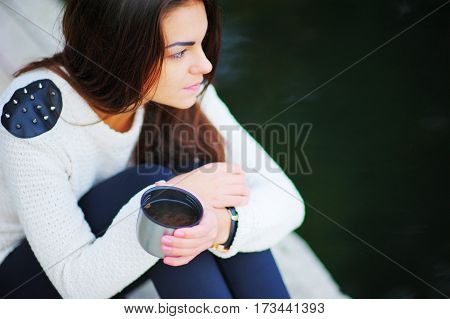 Beautiful brunette girl thoughtfully sitting with a cup of hot tea from a thermos on a cool autumn day side view close-up