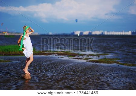 blonde in a white dress with a green scarf is standing on a stone in the middle of the water