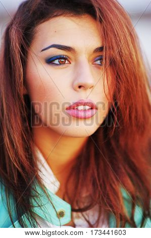 Portrait of a beautiful young confident woman in a turquoise jacket on the street on blurred background closeup.