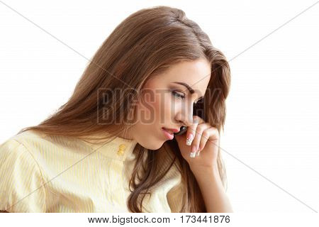 portrait of young beautiful woman talking on cellphone looking down isolated on white in photostudio