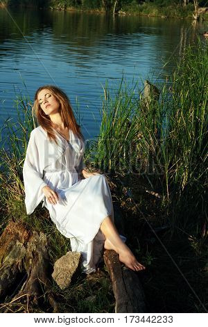 portrait of beautiful young woman in white dress resting on the lakeshore sitting surrounded with green grass